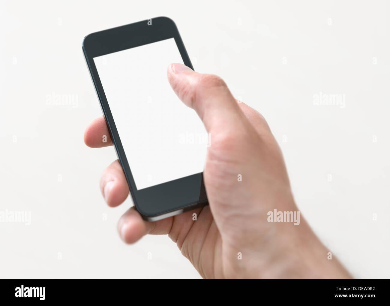 Maschio tenuta a mano e toccando sul mobile smartphone con schermo vuoto. Isolato su sfondo bianco. Immagini Stock