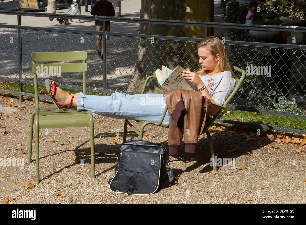 giovane donna seduta da sola nel parco Foto Stock