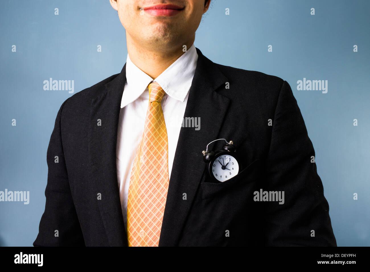 Giovane uomo d affari con un orologio nella sua tasca anteriore ha il tempo sul suo lato Immagini Stock