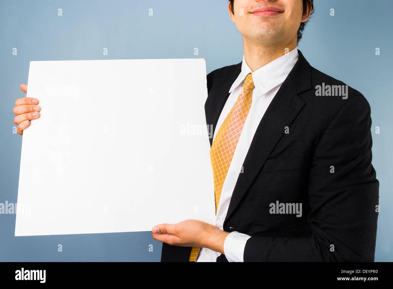 Happy businessman tenendo un vuoto segno bianco Immagini Stock