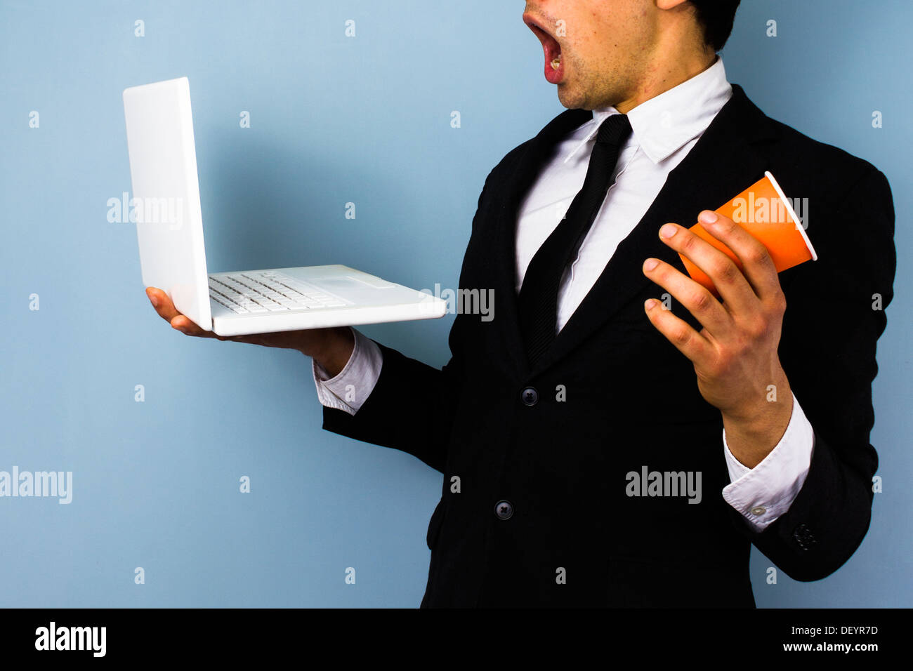 Giovane imprenditore è scioccata circa le notizie sul suo computer portatile e quasi il rovesciamento di liquidi il suo caffè Immagini Stock