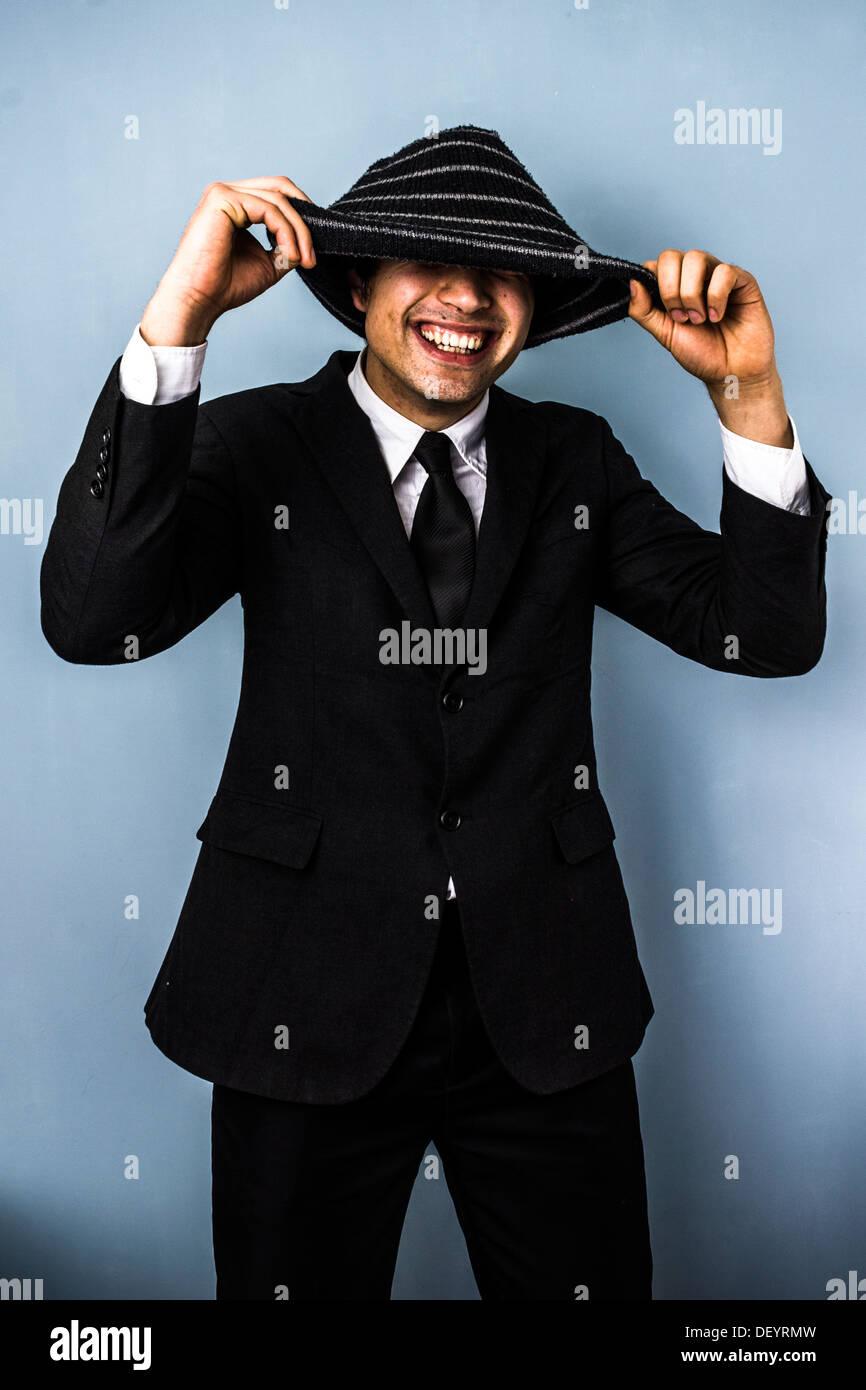 Giovane uomo d affari sorride da sotto il suo cappello di lana Immagini Stock