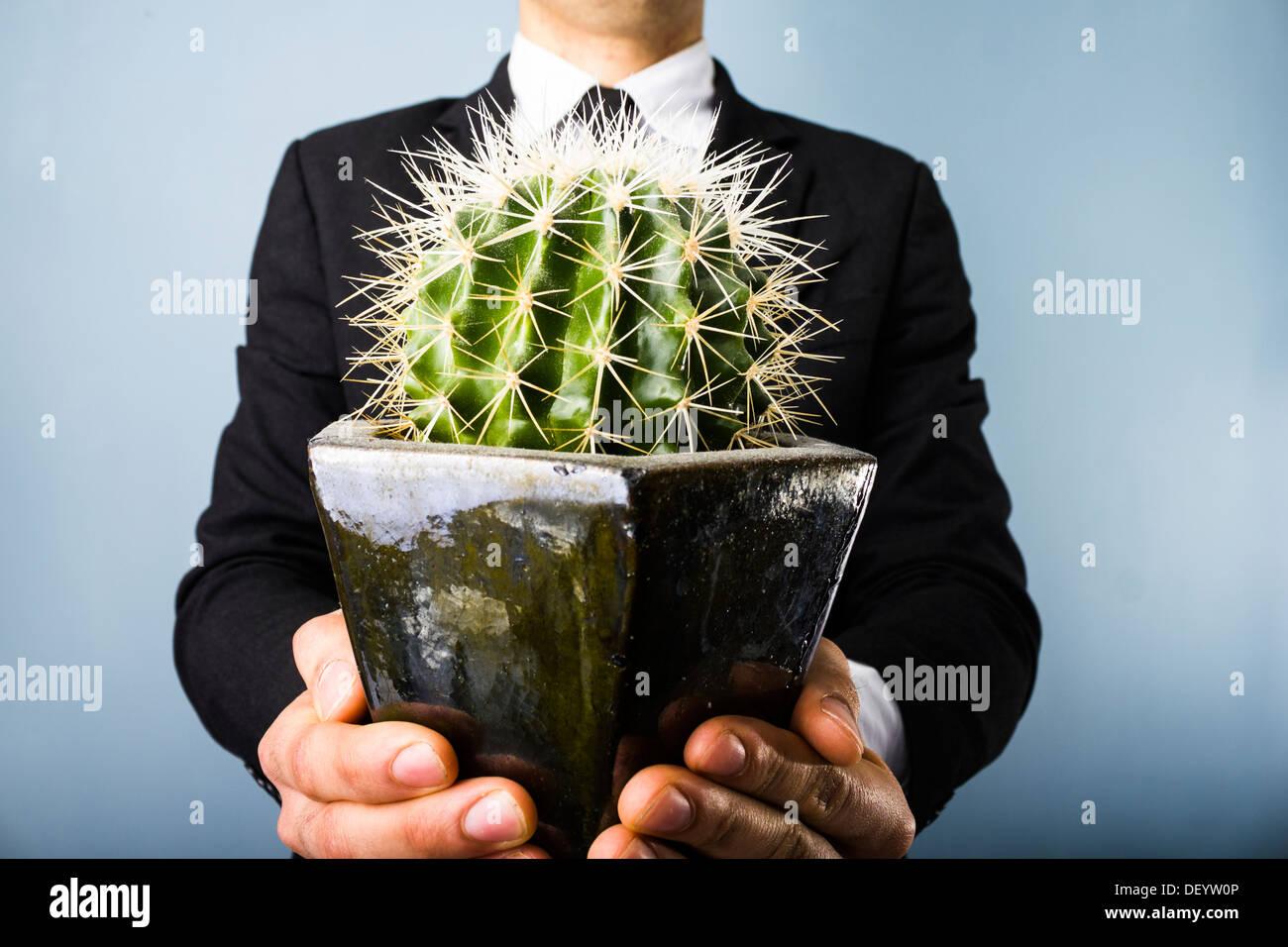 Giovane imprenditore che offre un cactus Immagini Stock