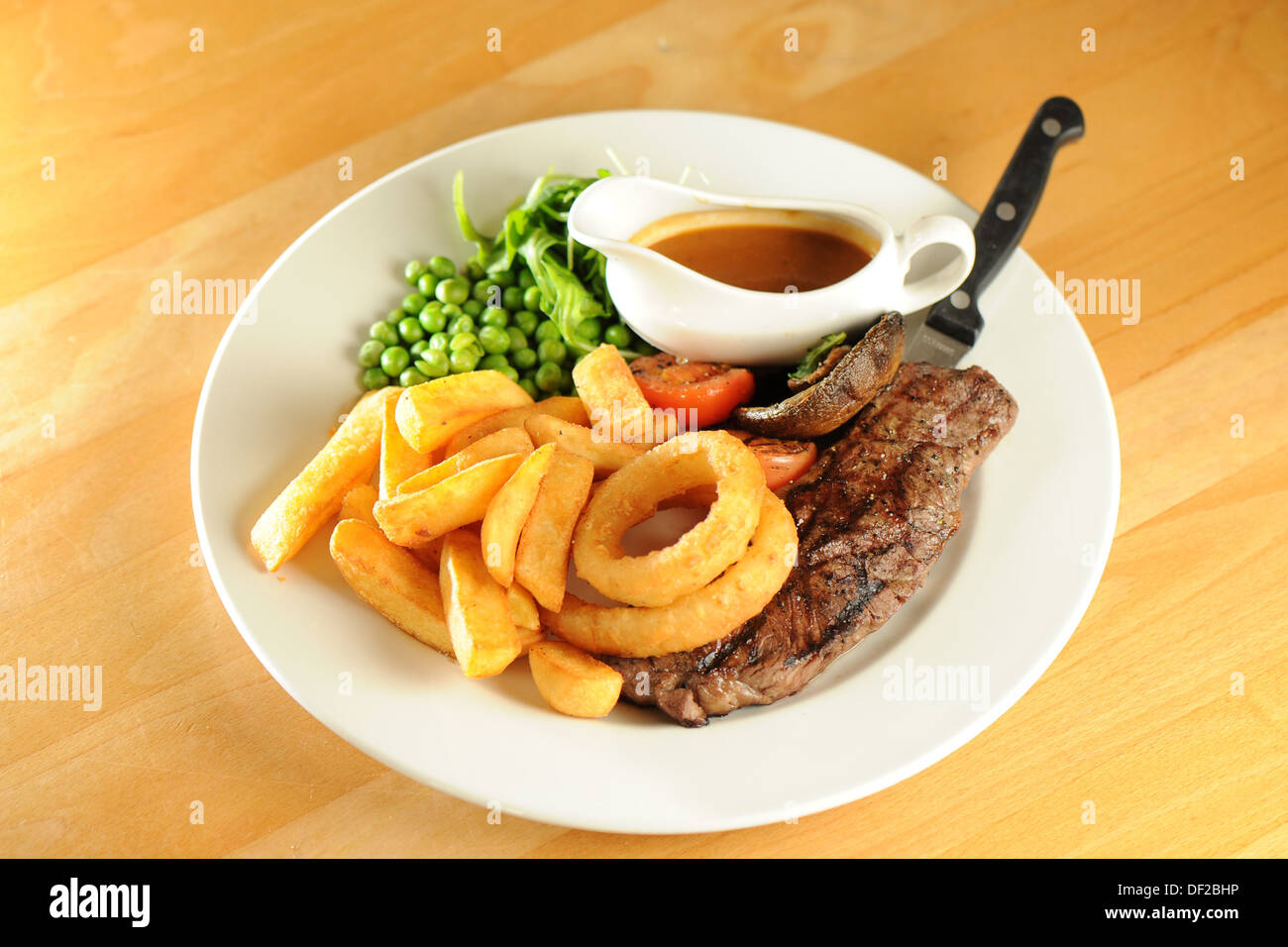 Tradizionali piatti da pub - bistecca di controfiletto, anelli di cipolla e piselli. Immagini Stock