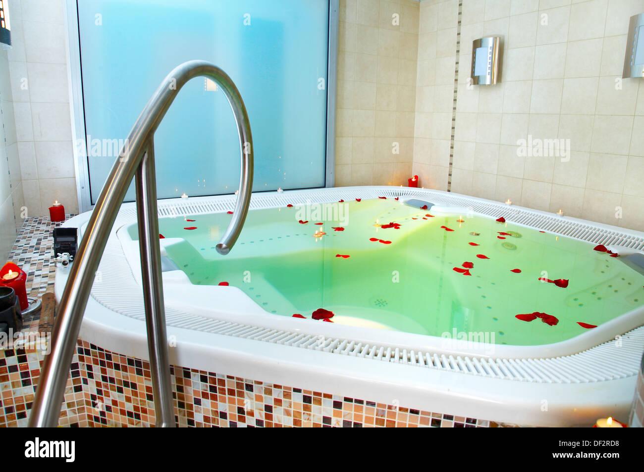 Vasca da bagno di jacuzzi con petali di rose foto immagine stock