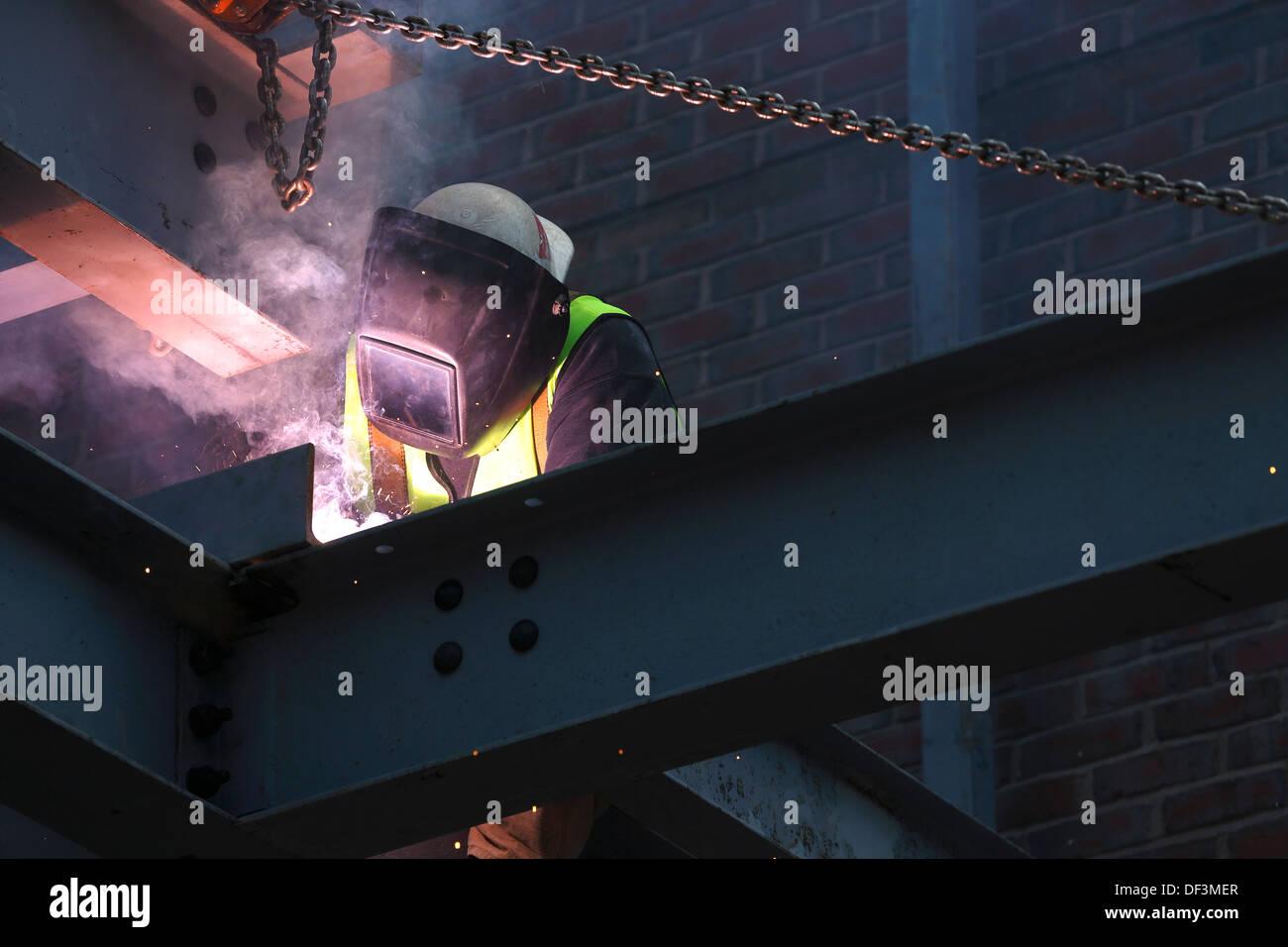 Lavoratore di ferro saldatore sul sito in costruzione Immagini Stock