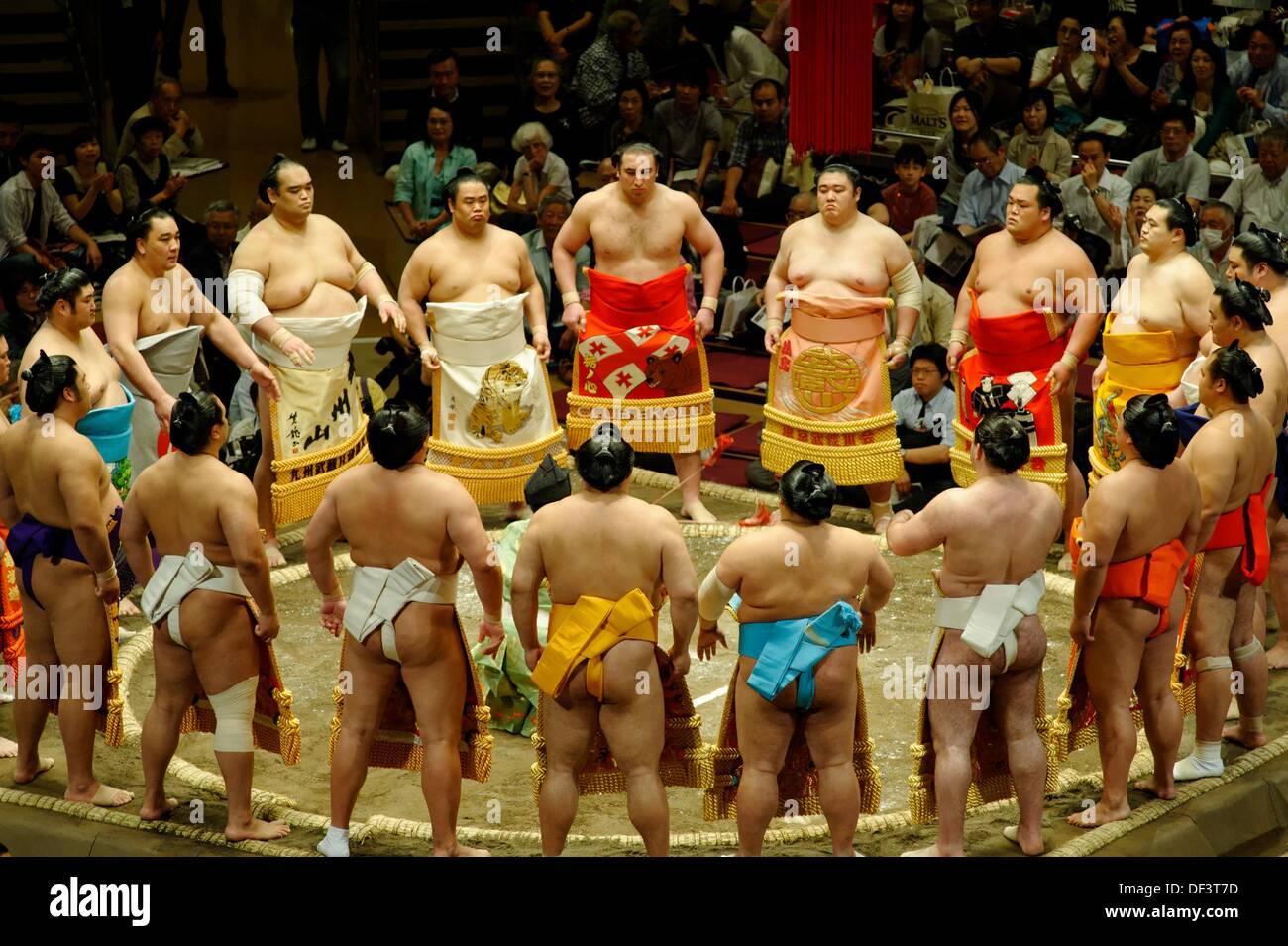 Lottatori di Sumo nel loro decorate grembiule cerimoniale kesho-mawashi si radunano in cerchio intorno al gyoji arbitro nel dohyo-iri, Immagini Stock
