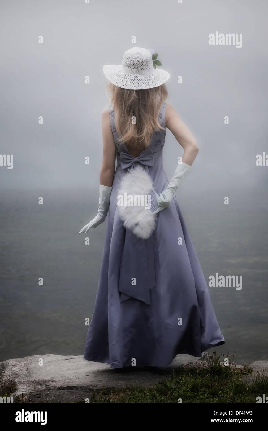 Una ragazza in un abito viola con cappello per il sole e la ventola è in piedi accanto a un lago Immagini Stock