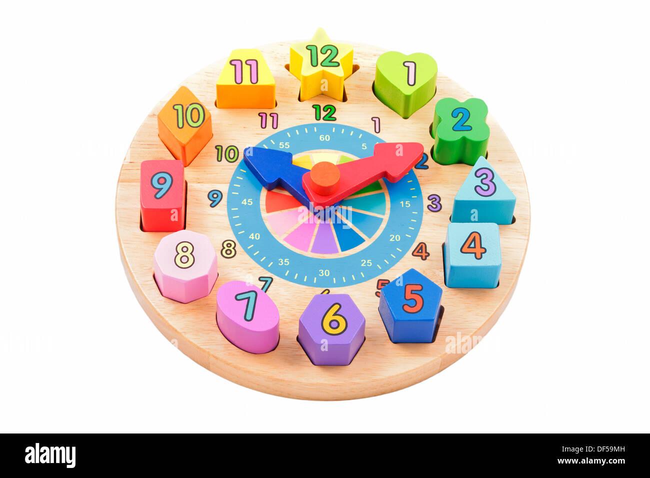 Bambino giocattolo orologio in legno con colorati numero di forme su sfondo bianco Immagini Stock