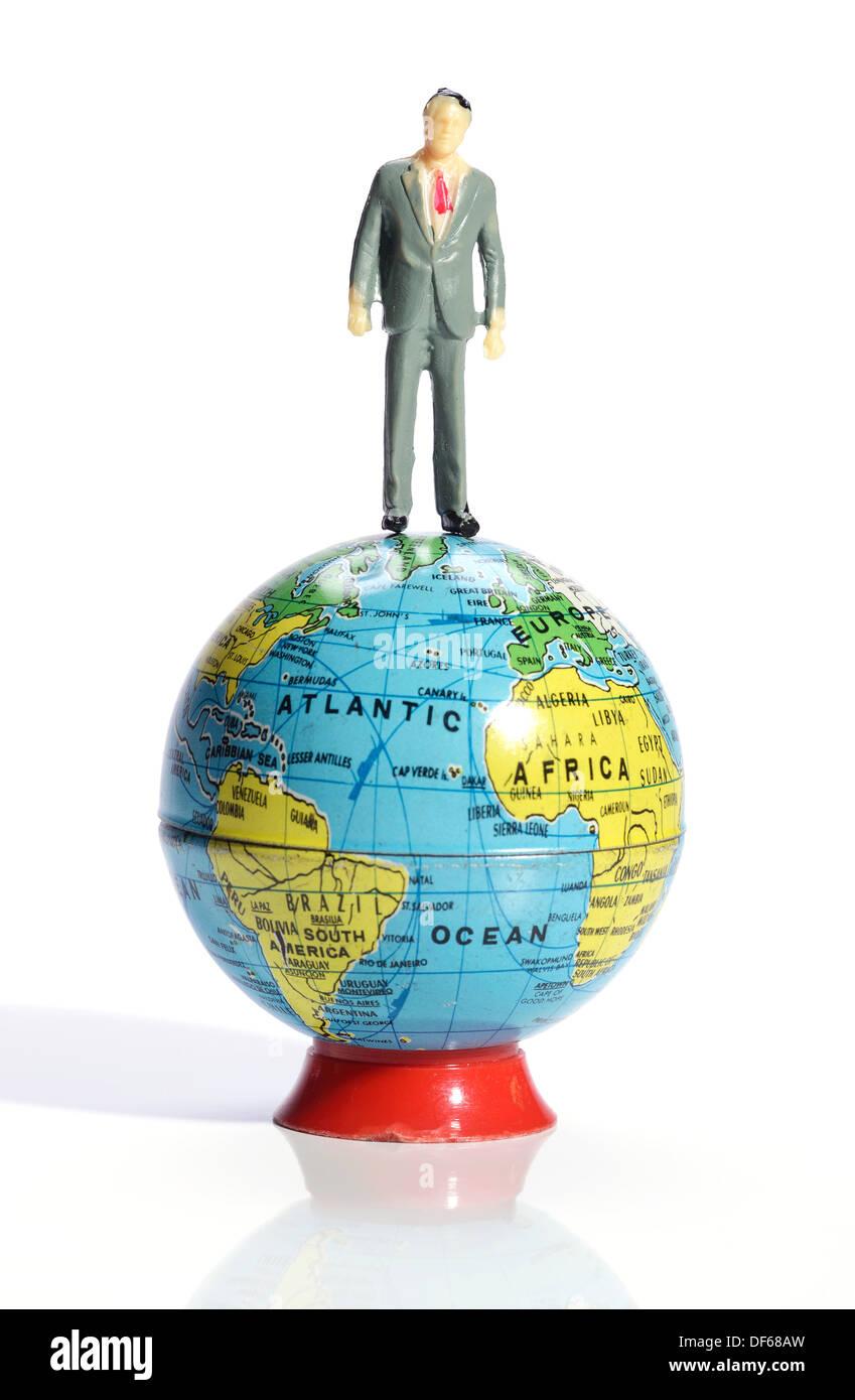 Business in plastica uomo in piedi in cima al mondo Immagini Stock