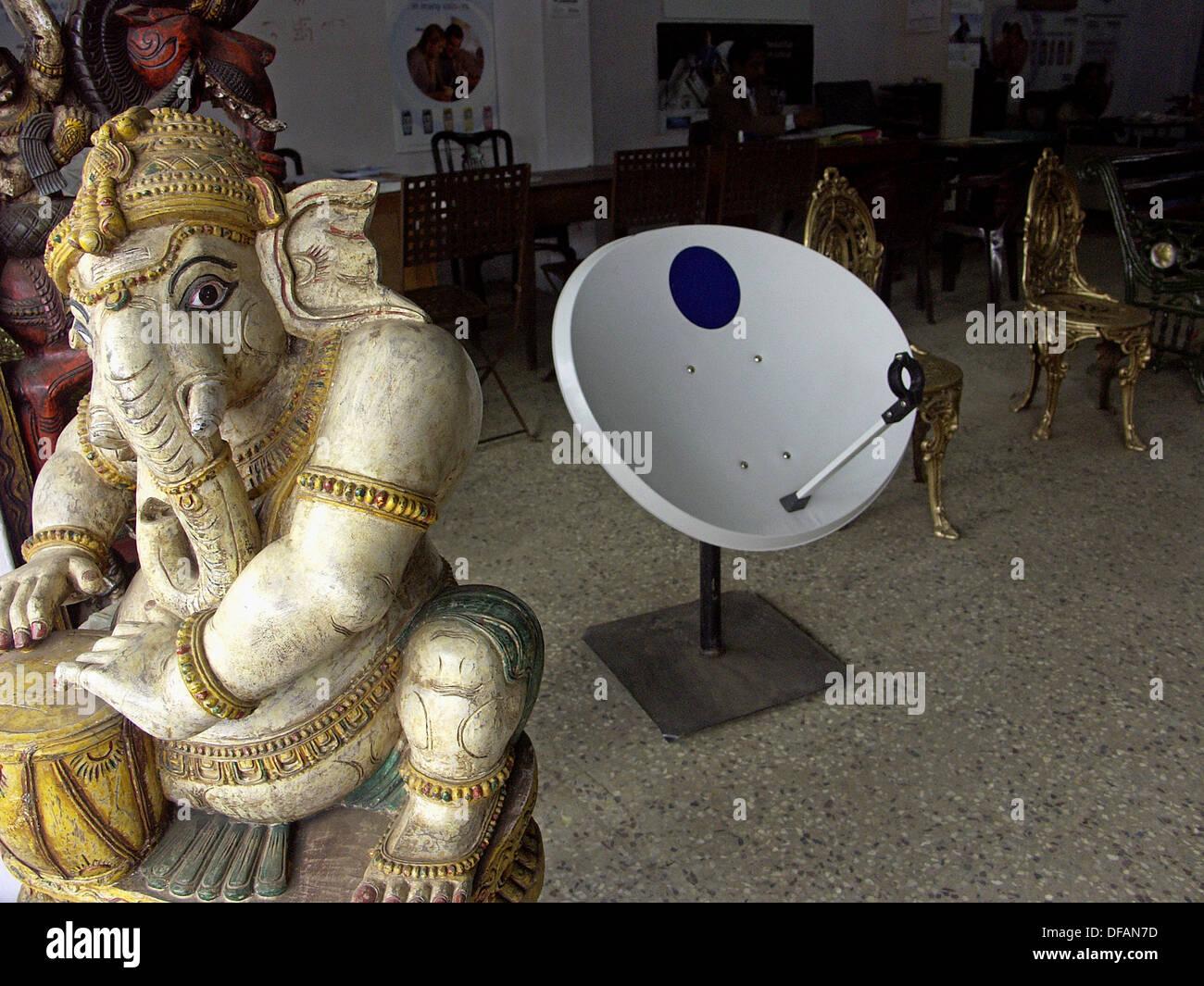 Satellite TV piatto e divinità Indù (Ganesha) condividono lo spazio di pavimento in un negozio. Ooty. Il Tamil Nadu, India Immagini Stock