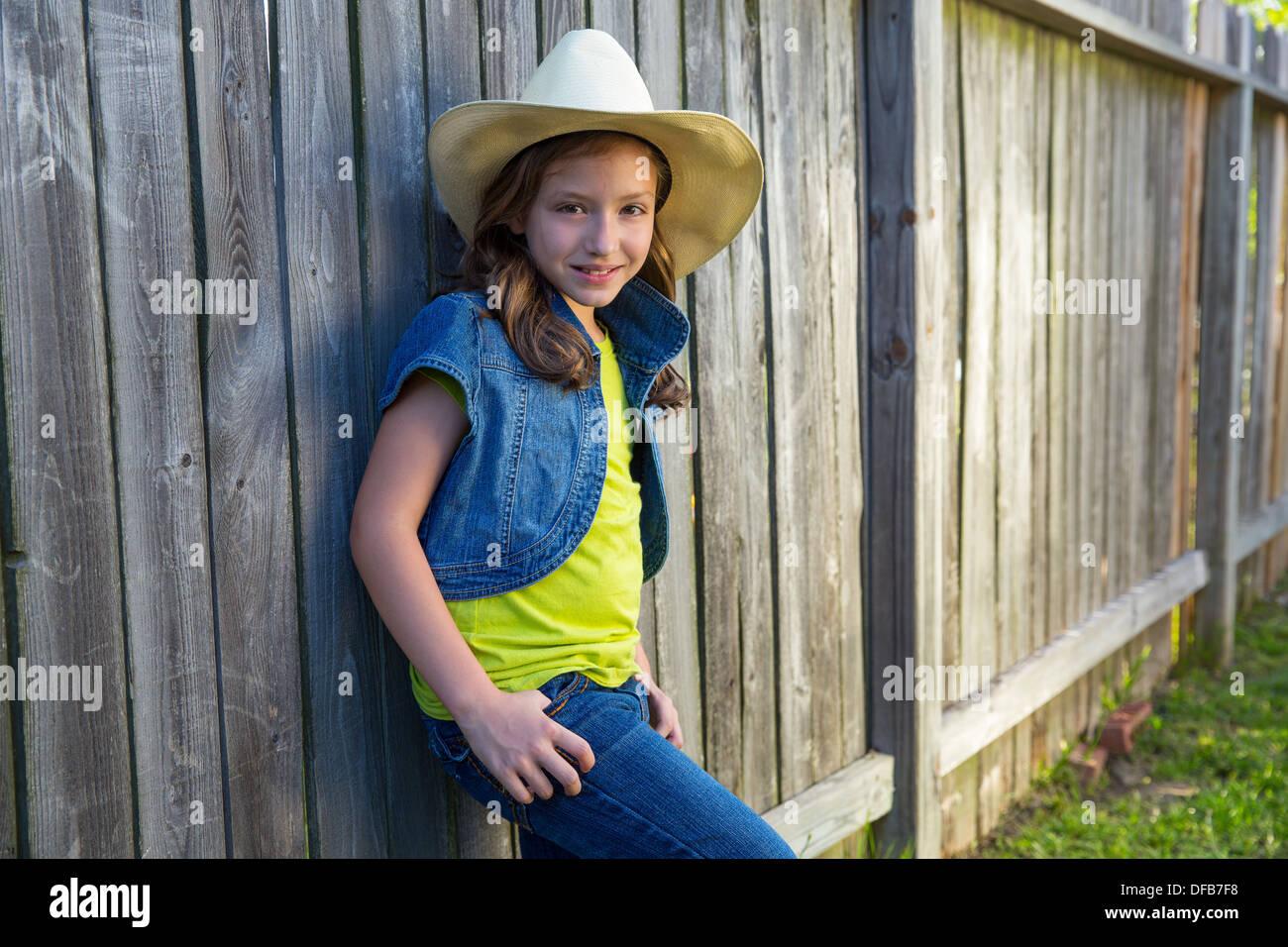 Bambini ragazza come kid cowboy ragazza cowgirl in posa sulla staccionata  in legno molto in stile occidentale c380927c1a6b