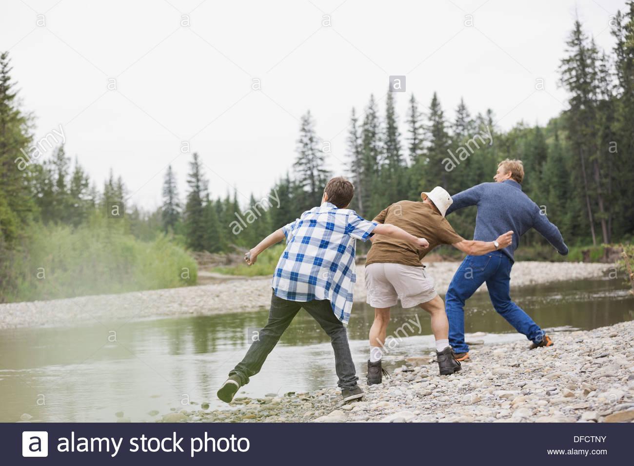 Membri maschi della famiglia il salto di rocce sulle rive di un fiume Immagini Stock