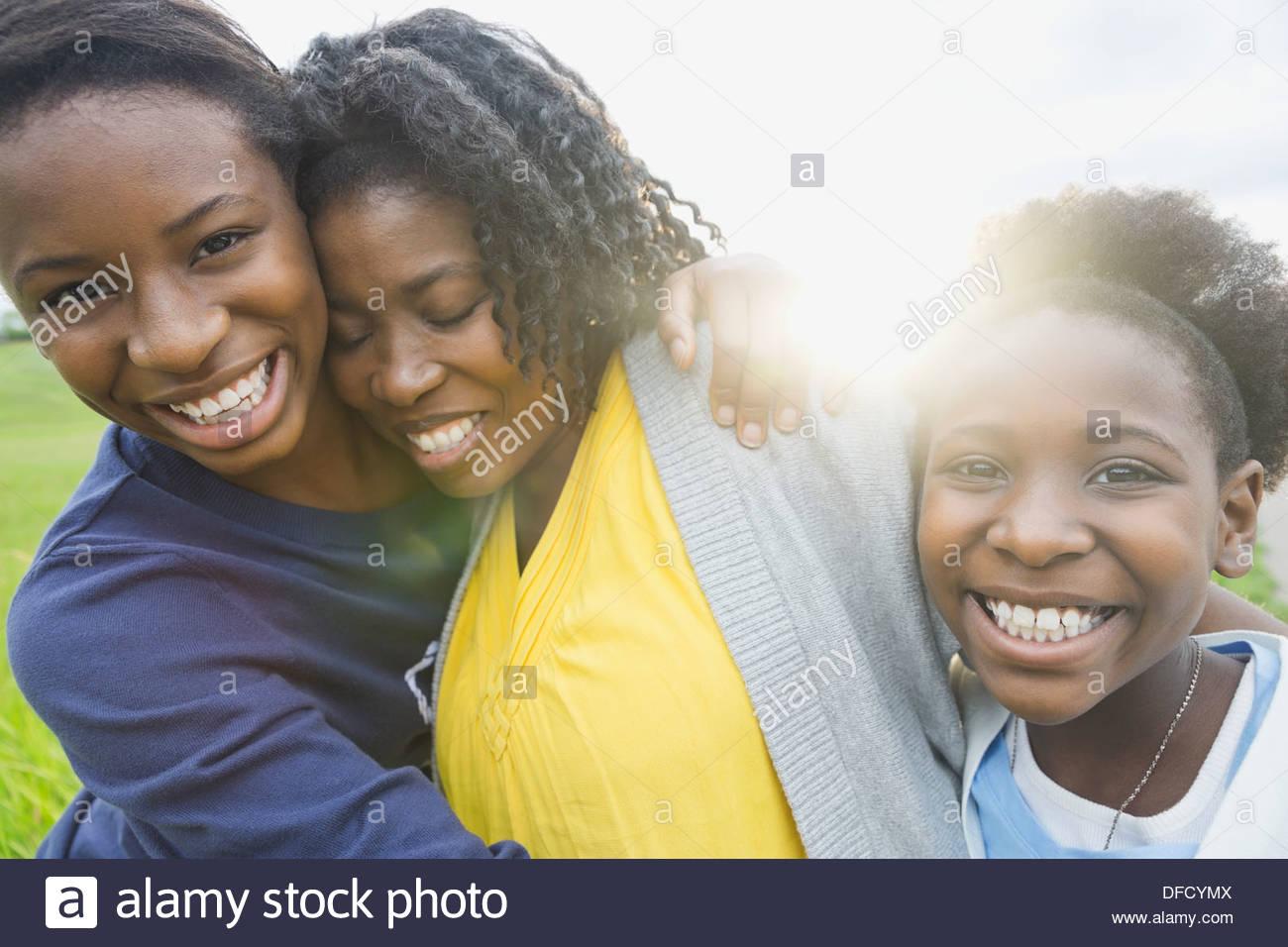 Ritratto di felice figlie abbracciando la madre all'aperto Immagini Stock