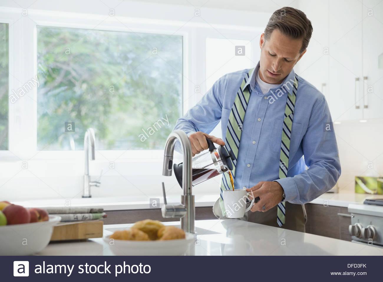 Imprenditore versando il caffè in cucina domestica Immagini Stock