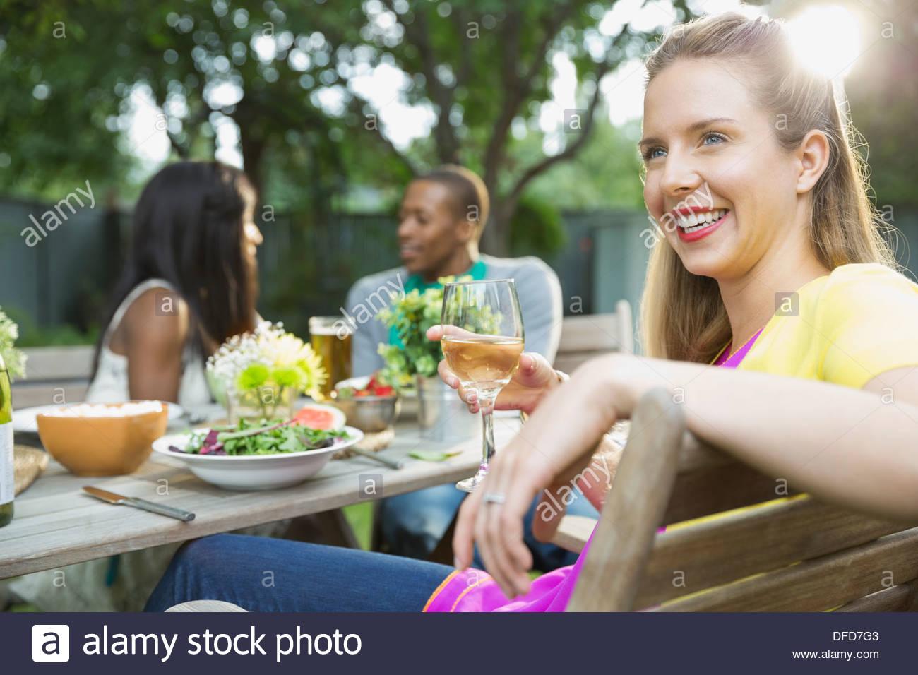 Donna sorridente con pasto con amici all'aperto Immagini Stock