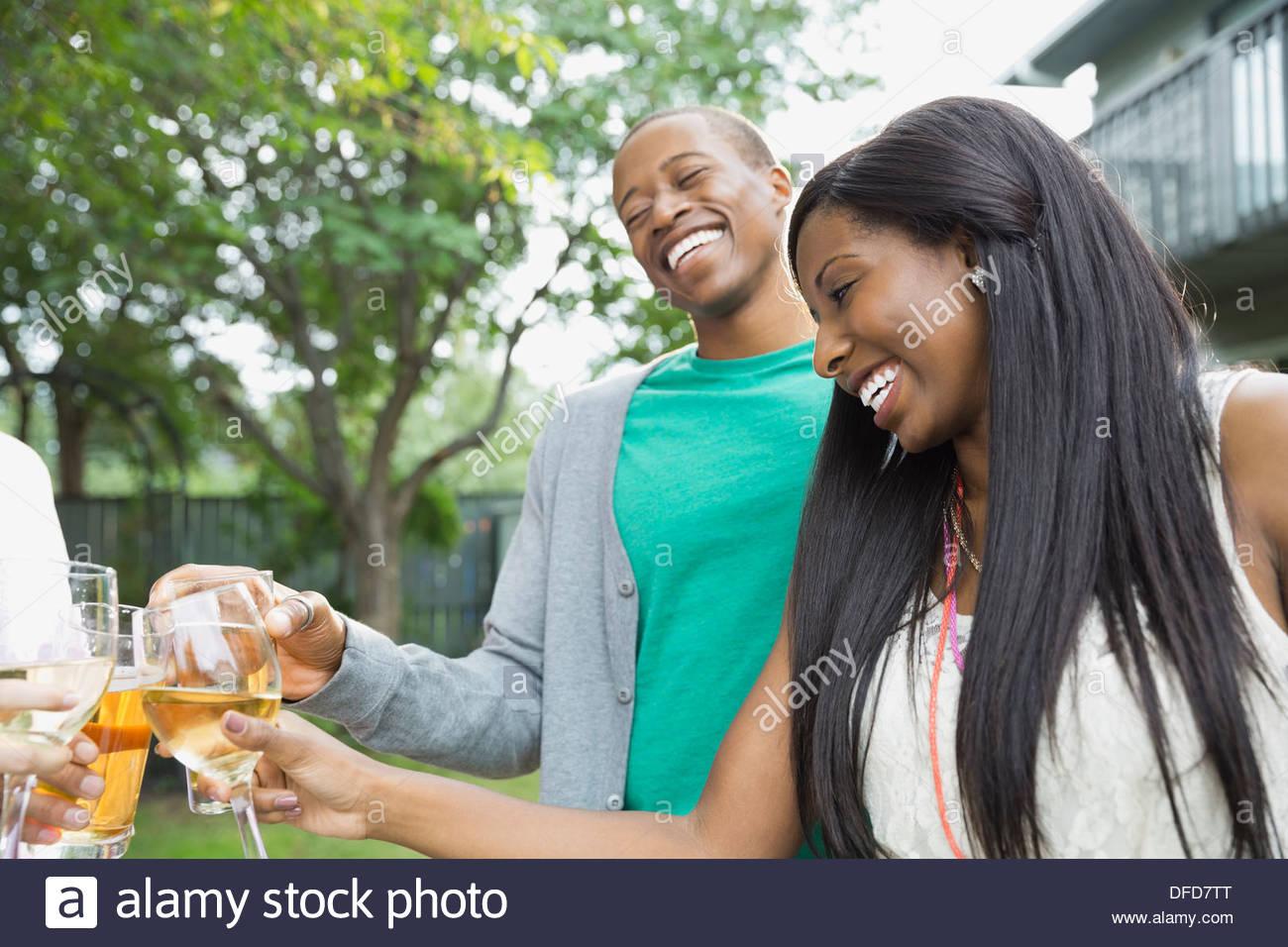 Allegro giovane tostare un drink con amici in esterno Immagini Stock