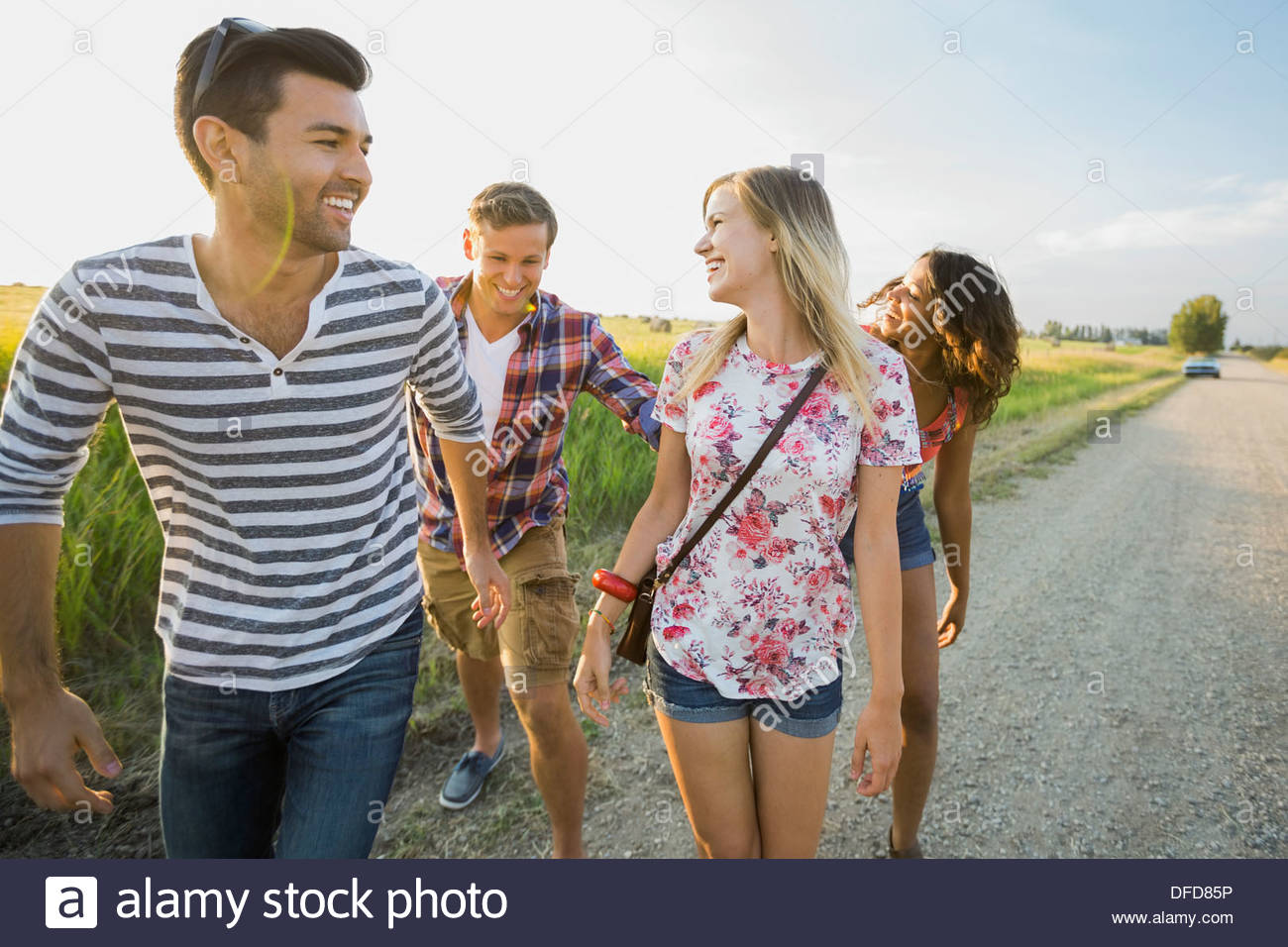 Gruppo di amici passeggiando per le strade di campagna Immagini Stock