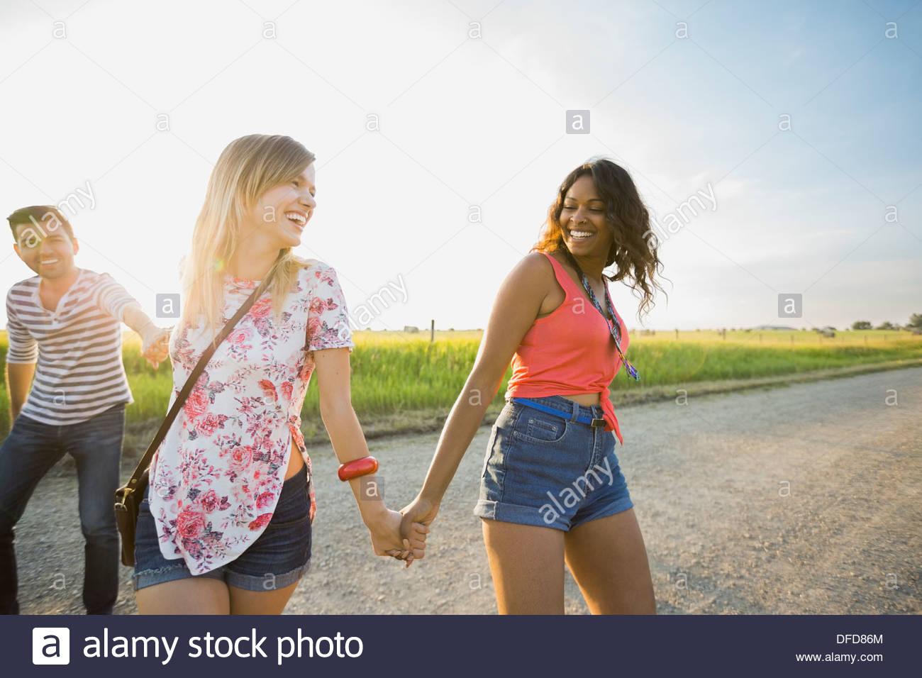 Gli amici passeggiando per le strade di campagna tenendo le mani Immagini Stock