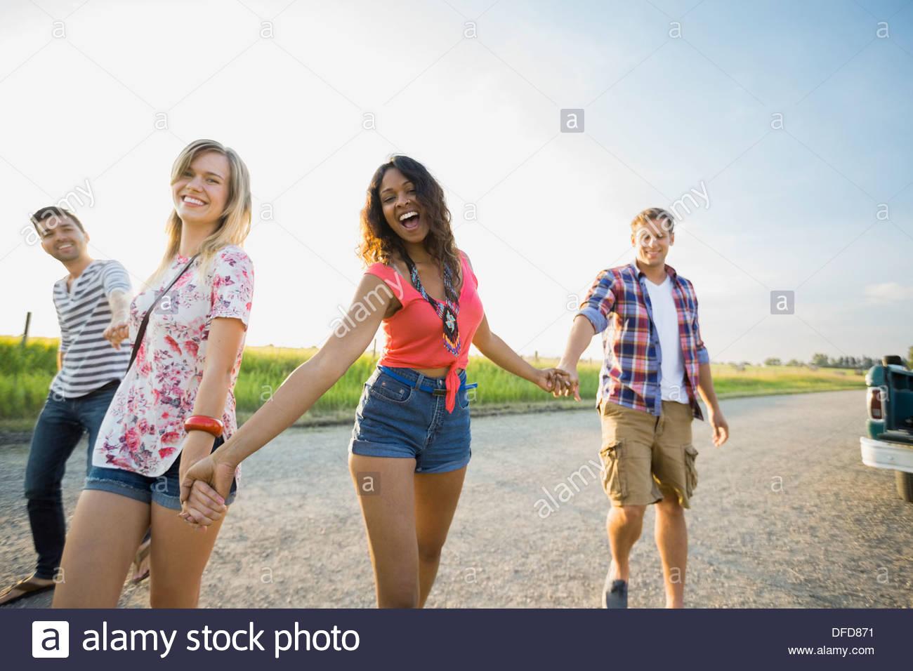 Gruppo di amici passeggiando per le strade di campagna tenendo le mani Immagini Stock