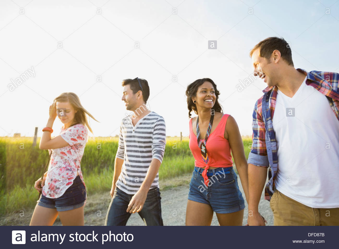 Giovani amici camminando sulla strada di campagna Immagini Stock