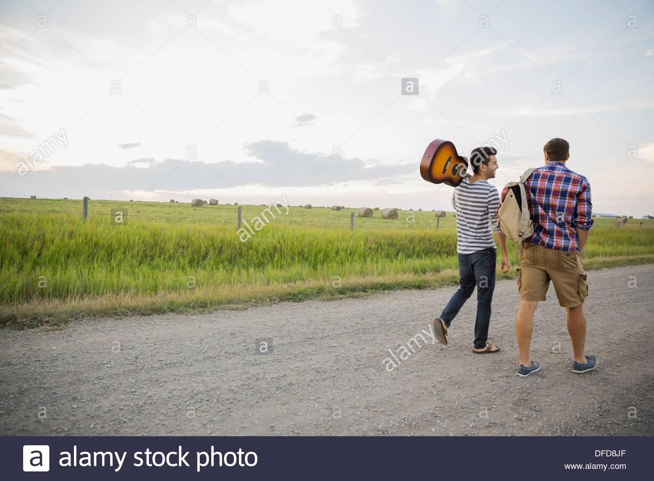 I giovani con la chitarra e zaino camminando sulla strada di campagna Immagini Stock