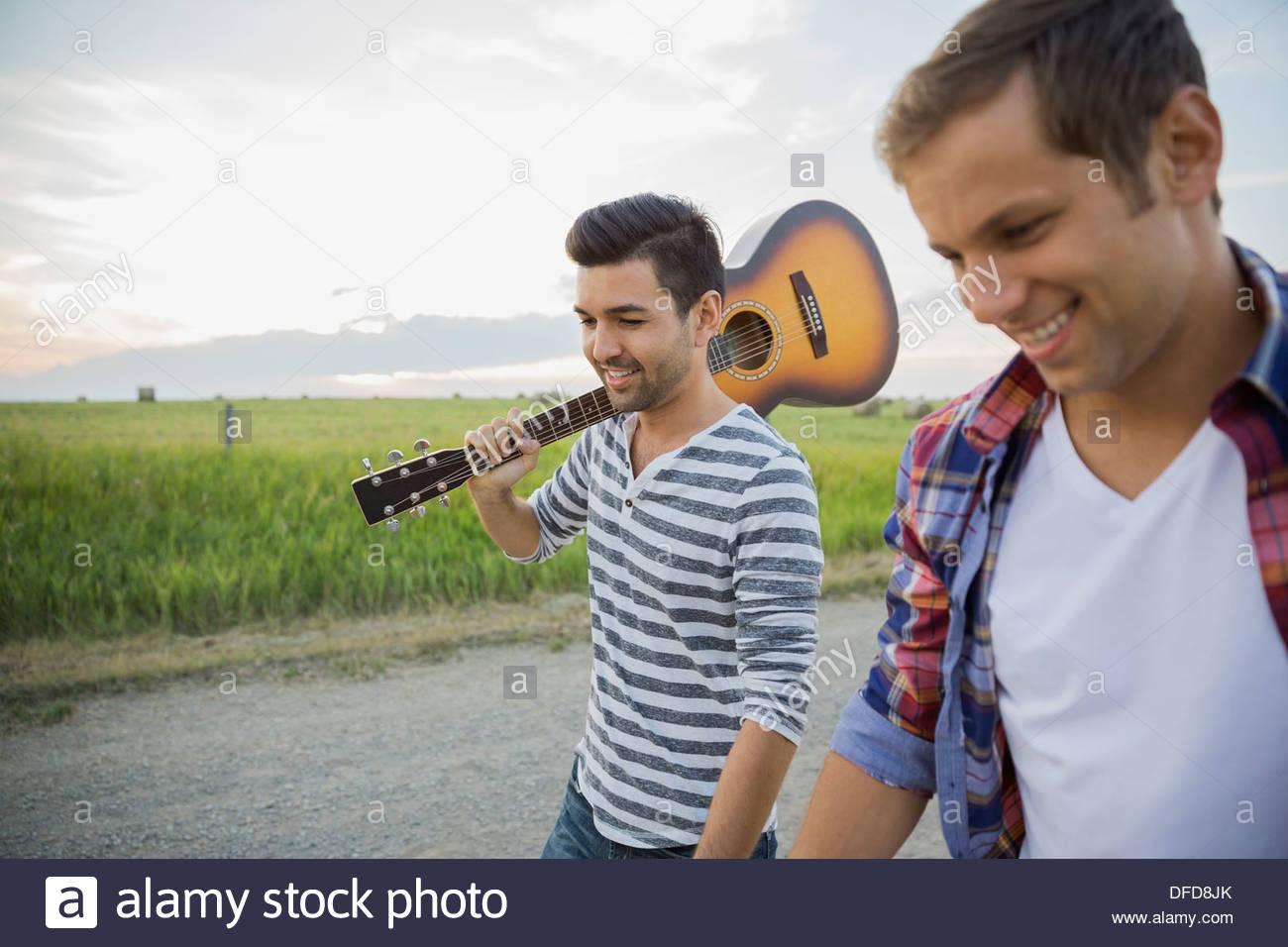 Giovani uomini con la chitarra a camminare sulla strada di campagna Immagini Stock