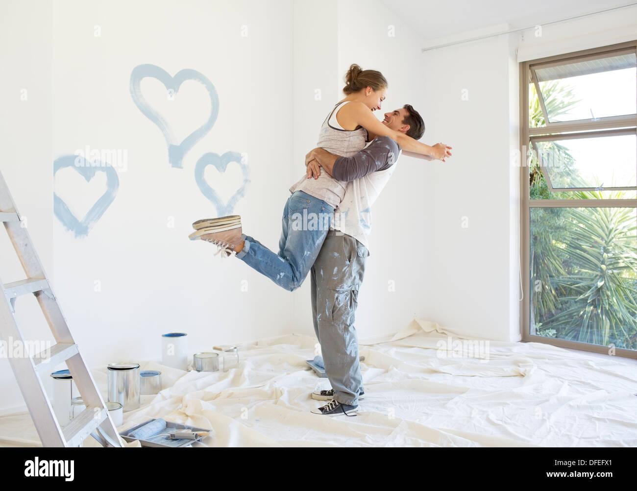 Giovane pittura cuori blu sulla parete Immagini Stock