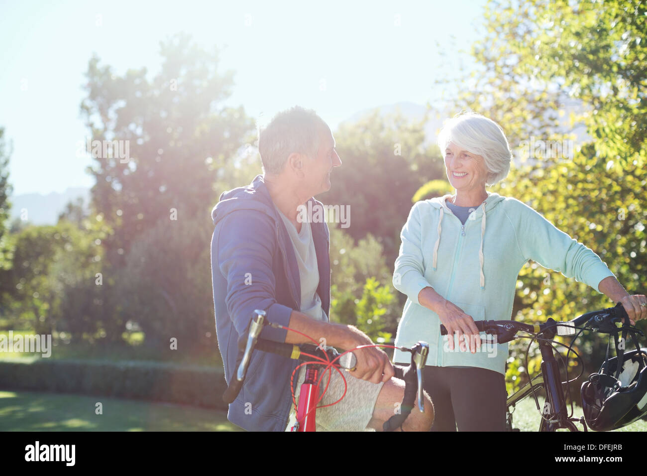 Coppia senior con le biciclette in posizione di parcheggio Immagini Stock