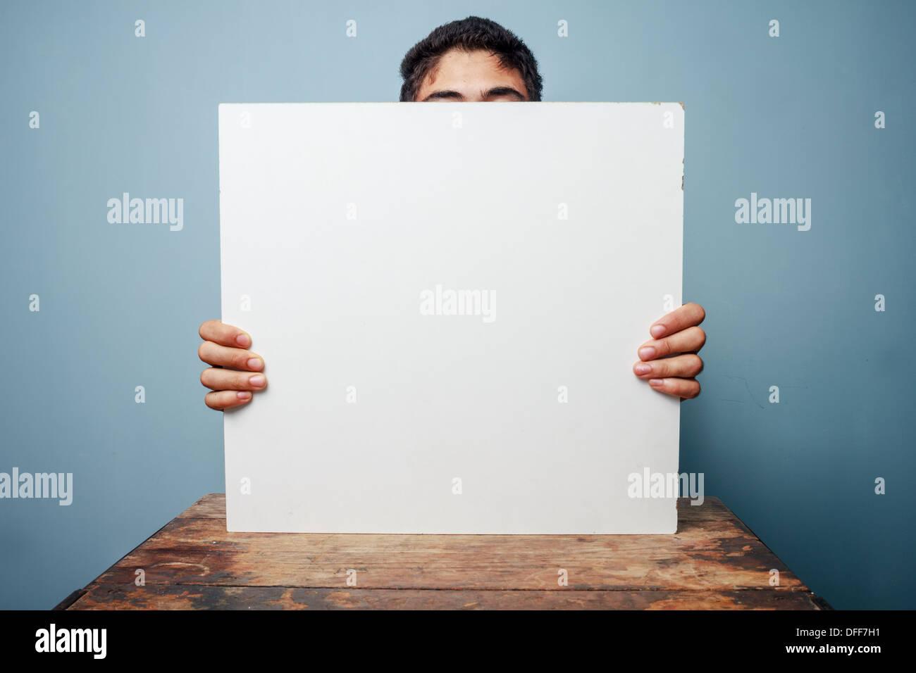 Giovane uomo seduto a un tavolo e tenendo un vuoto segno bianco, solo la cima della sua testa è visibile Immagini Stock