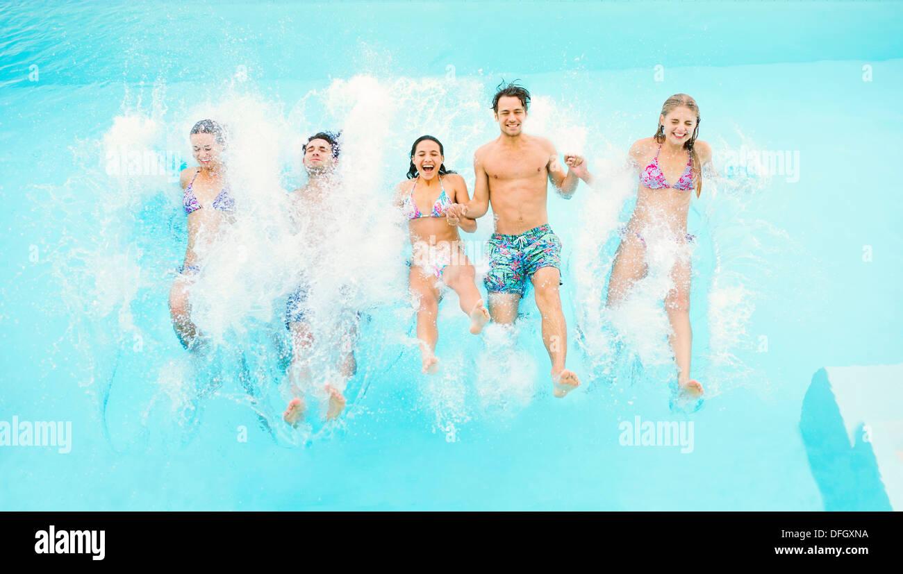 Gli amici il salto in piscina Immagini Stock