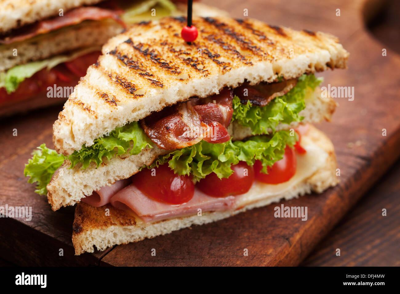 Chiusura del sandwich freschi con prosciutto, pancetta, pomodori, formaggi e lattuga Immagini Stock