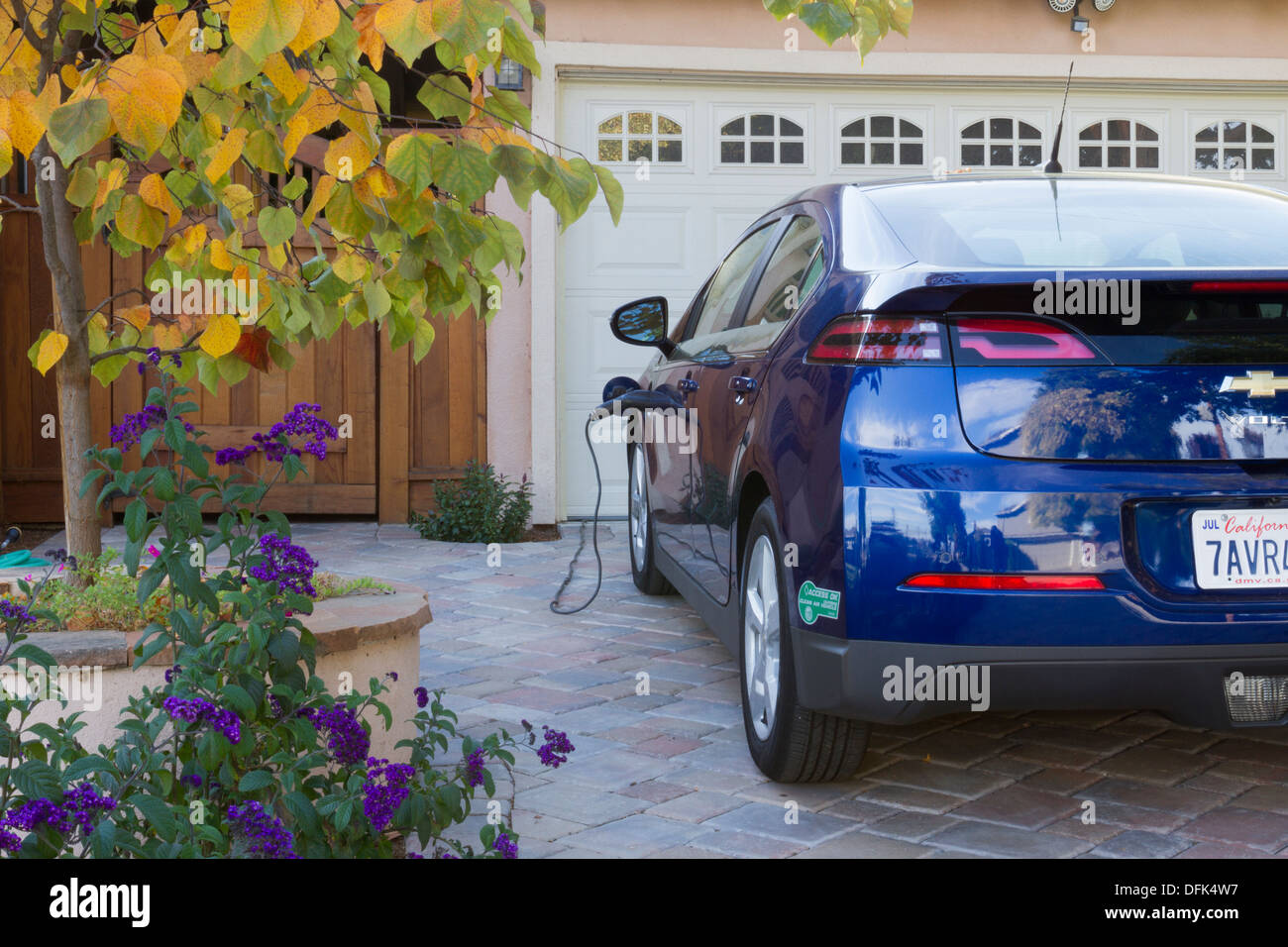 Plug-in auto elettrica con adesivo carpool parcheggiato nel viale di accesso con il connettore collegato alla presa di corrente e caricare a casa Immagini Stock