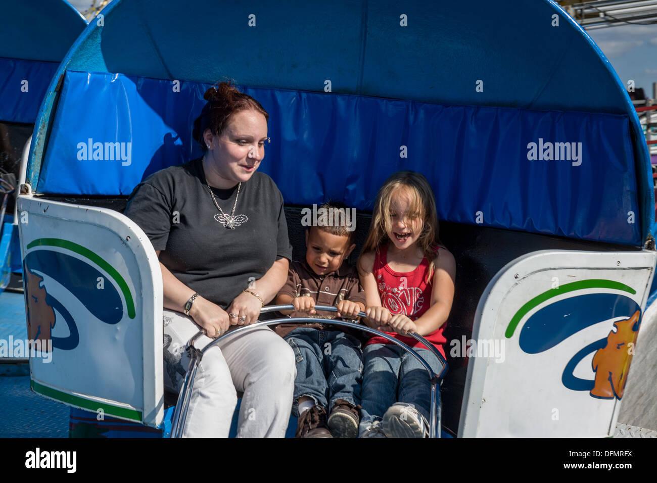 La madre ed i suoi figli piccoli su Tilt-a-vortice, Grande New York State Fair. Immagini Stock