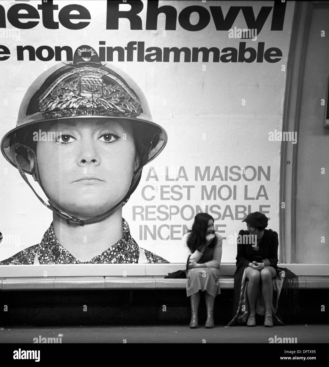 """Due donne siedono sotto un annuncio pubblicitario per tessuti sintetici e di parlare a Parigi nel novembre 1970. Il messaggio pubblicitario loda l'infiammabilità del materiale. Lo slogan recita: 'a casa, io sono responsabile per la conflagrazione."""" Foto: Wilfried Glienke Foto Stock"""