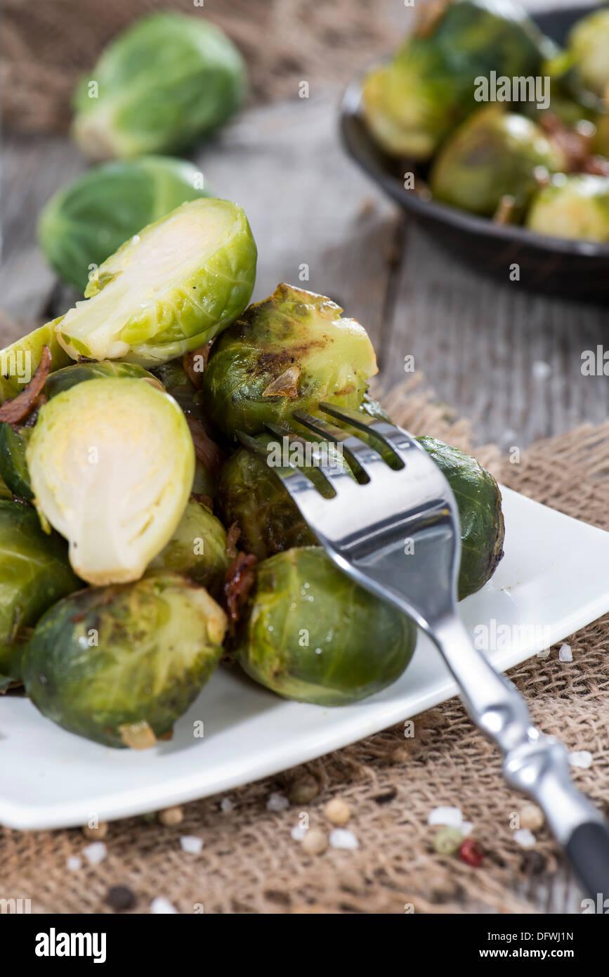 Porzione di fritto i cavoletti di Bruxelles con prosciutto e le cipolle Foto Stock