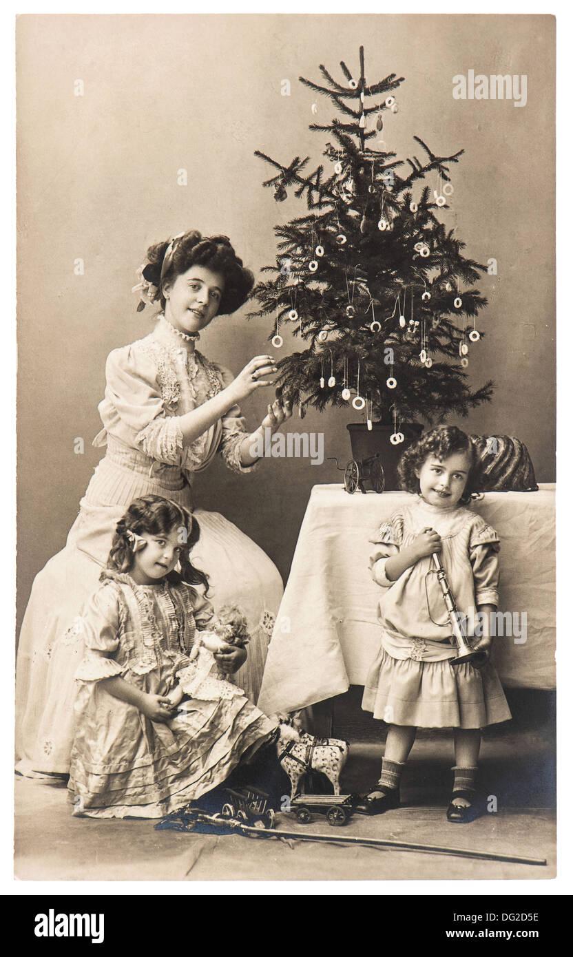 Antico ritratto di famiglia della madre e bambini con albero di natale di indossare abbigliamento vintage Immagini Stock