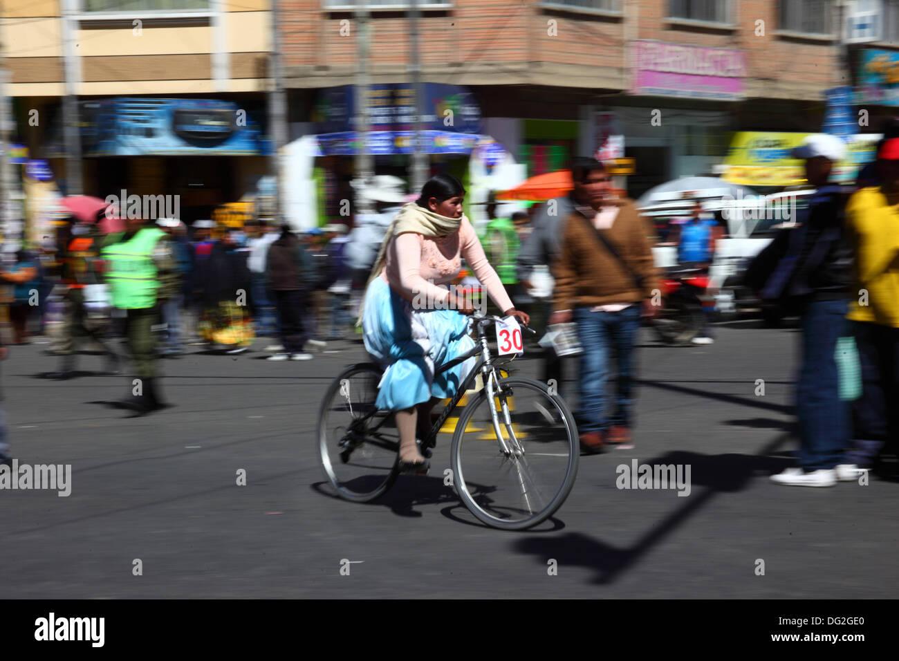 El Alto in Bolivia. Xii oct, 2013. Un concorrente passa di spettatori come lei prende parte a una bicicletta Cholitas Foto Stock