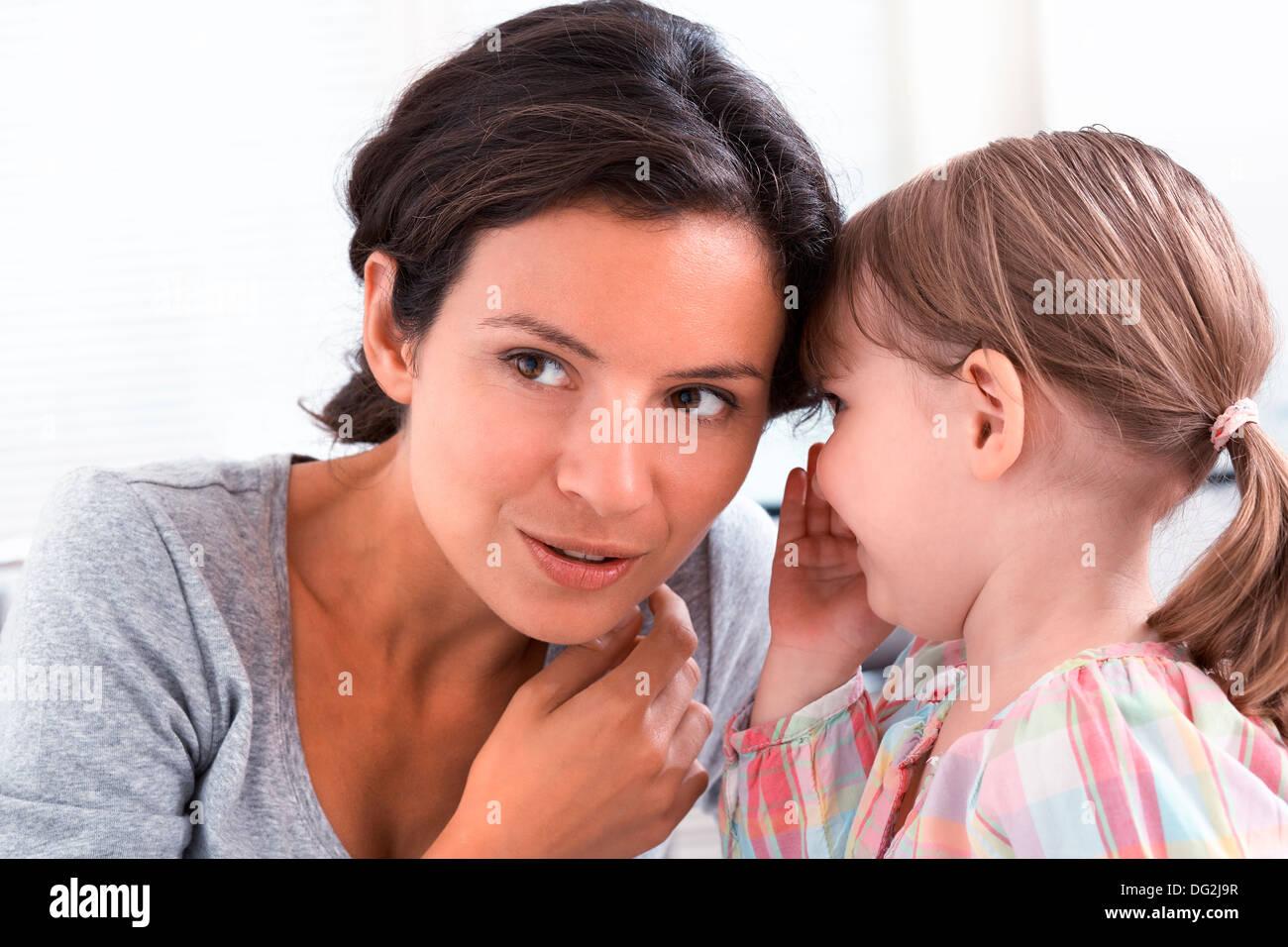 Felice madre con sua figlia dicendo un segreto di porte Immagini Stock