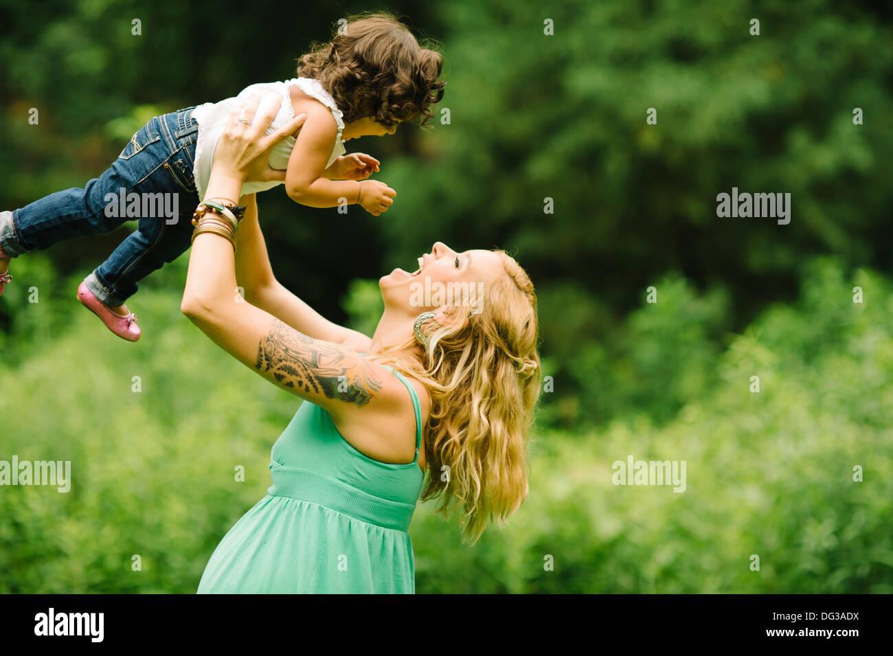 Donna Incinta solleva il bambino sopra la testa Foto Stock
