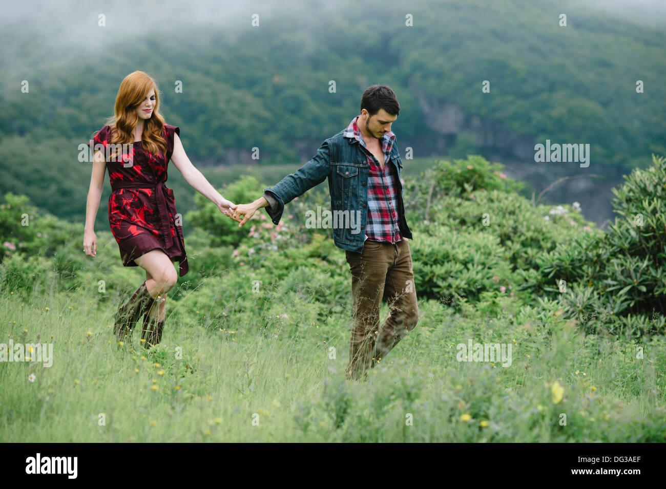 Coppia giovane tenendo le mani mentre si cammina attraverso il campo Immagini Stock