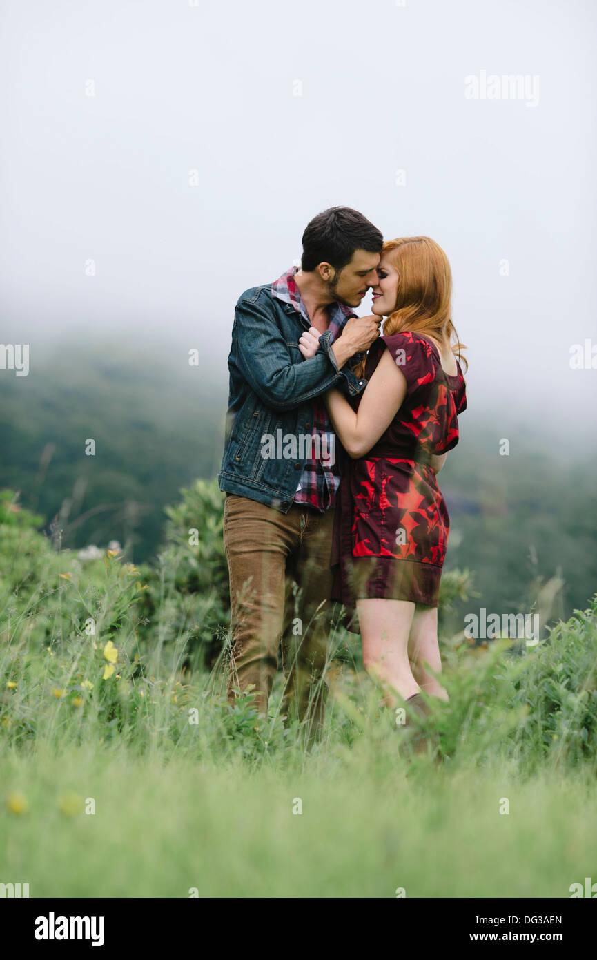 Coppia romantica circa al bacio nel campo di nebbia Immagini Stock