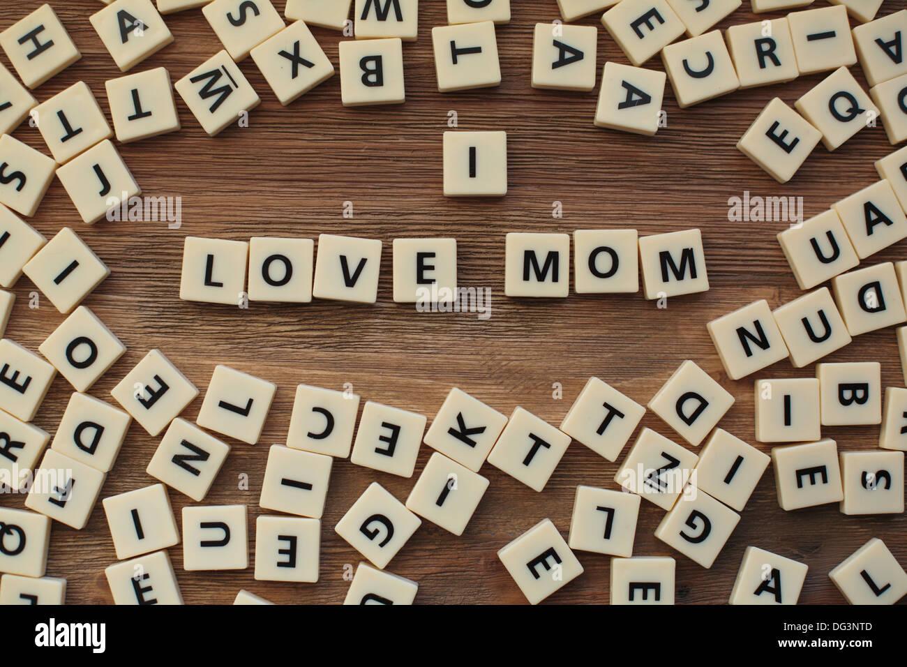 """Lettere di plastica da un childrens' ortografia gioco su un tavolo in legno scrivi """"Io amo mamma"""" Immagini Stock"""
