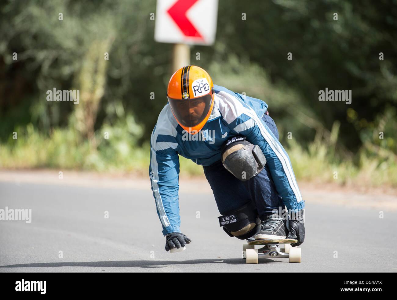 Skateboard longboard uomo training su strada pubblica, in discesa Immagini Stock
