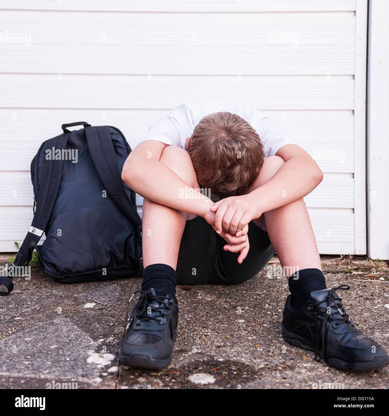 Un ragazzo di 10 guardando triste e depresso nella sua uniforme scolastica che mostra gli effetti di bullismo nel Regno Unito Immagini Stock