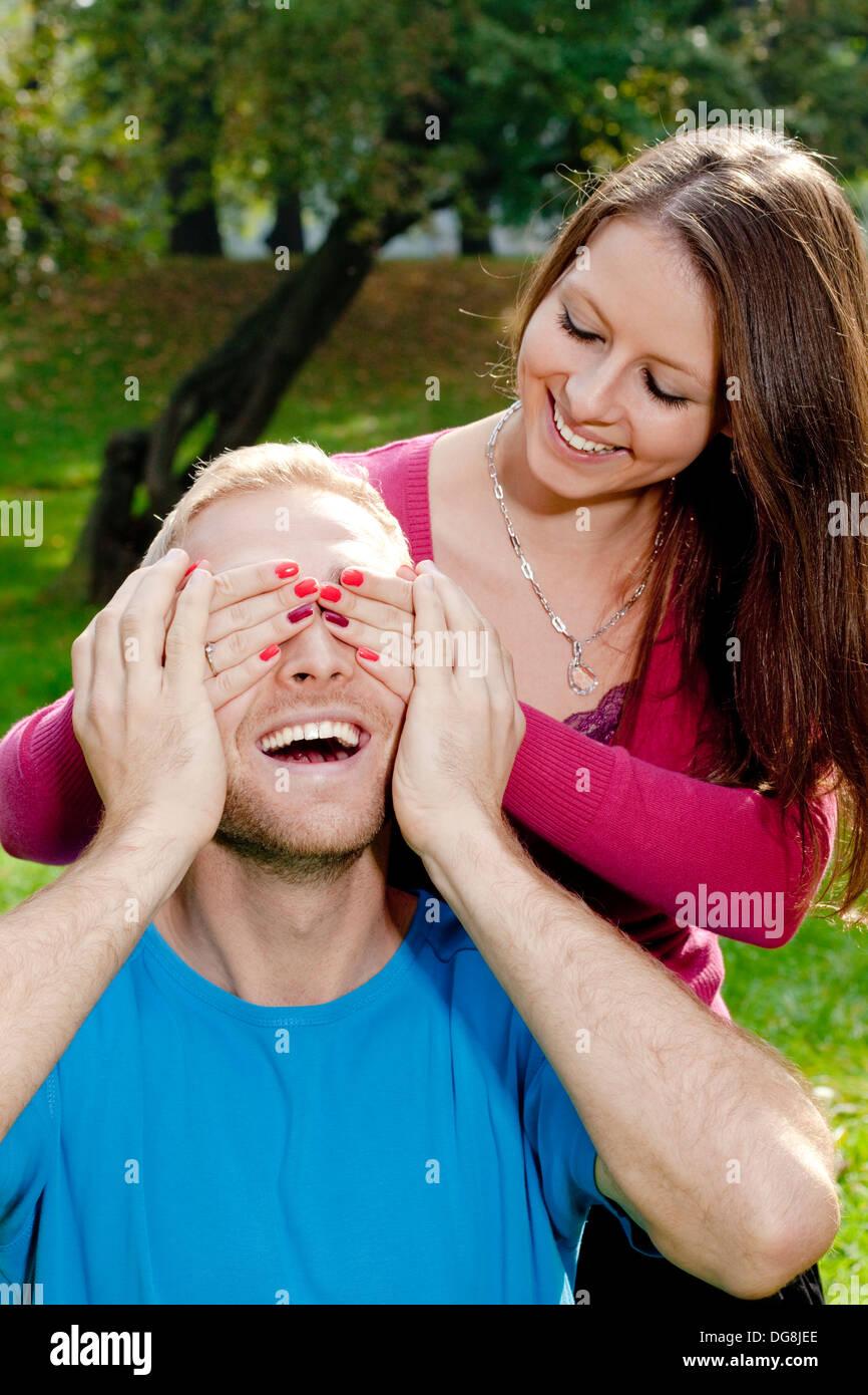 Ragazza giovane che copre i suoi fidanzati gli occhi per la sorpresa di lui Immagini Stock