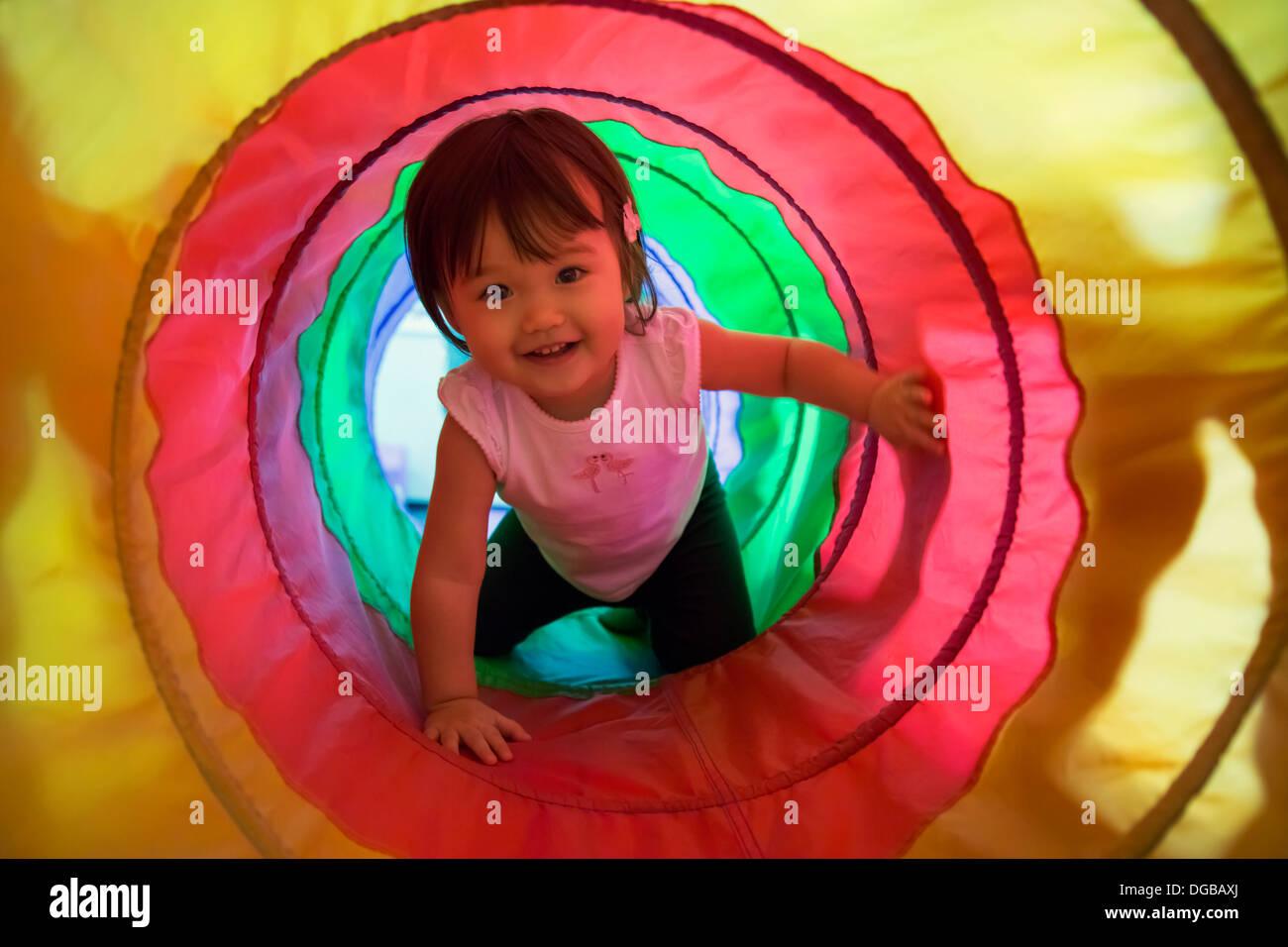 Baby girl strisciando attraverso il tunnel di riproduzione Immagini Stock