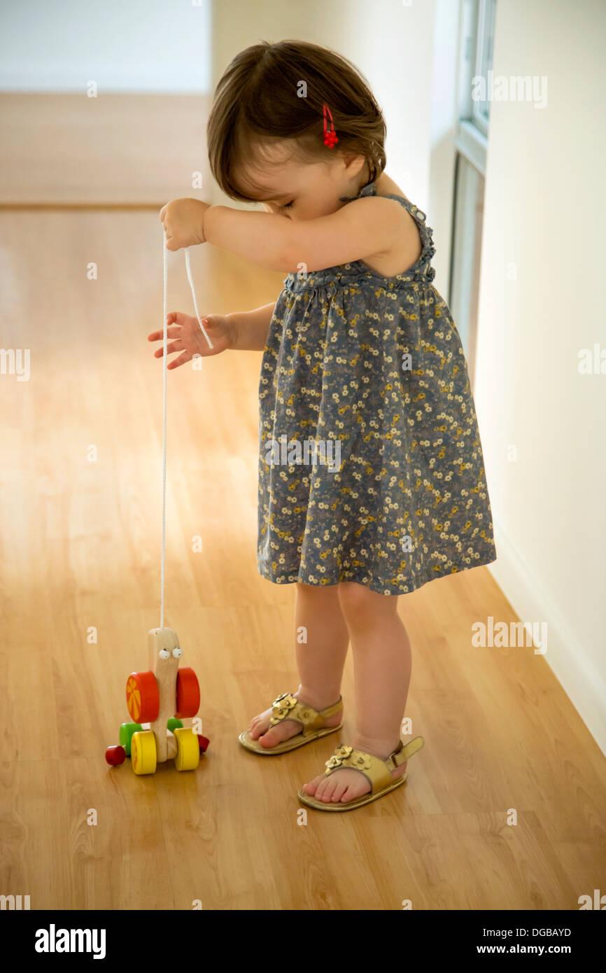 Baby girl giocare con un giocattolo di legno su una stringa Immagini Stock