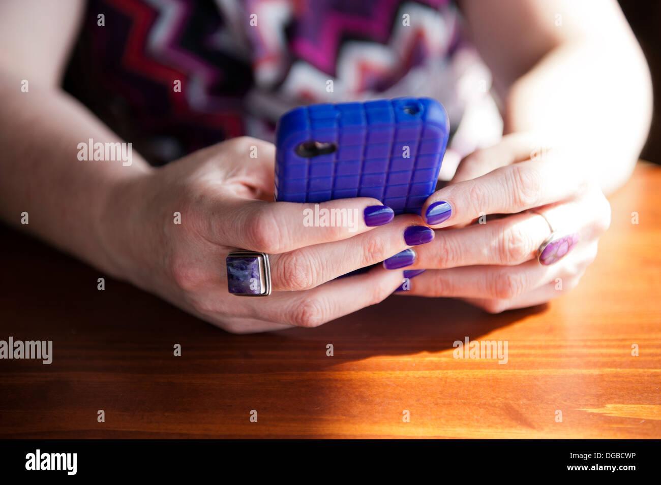 Signora tenendo un telefono intelligente con un caso di porpora e corrispondenza di unghie. Immagini Stock
