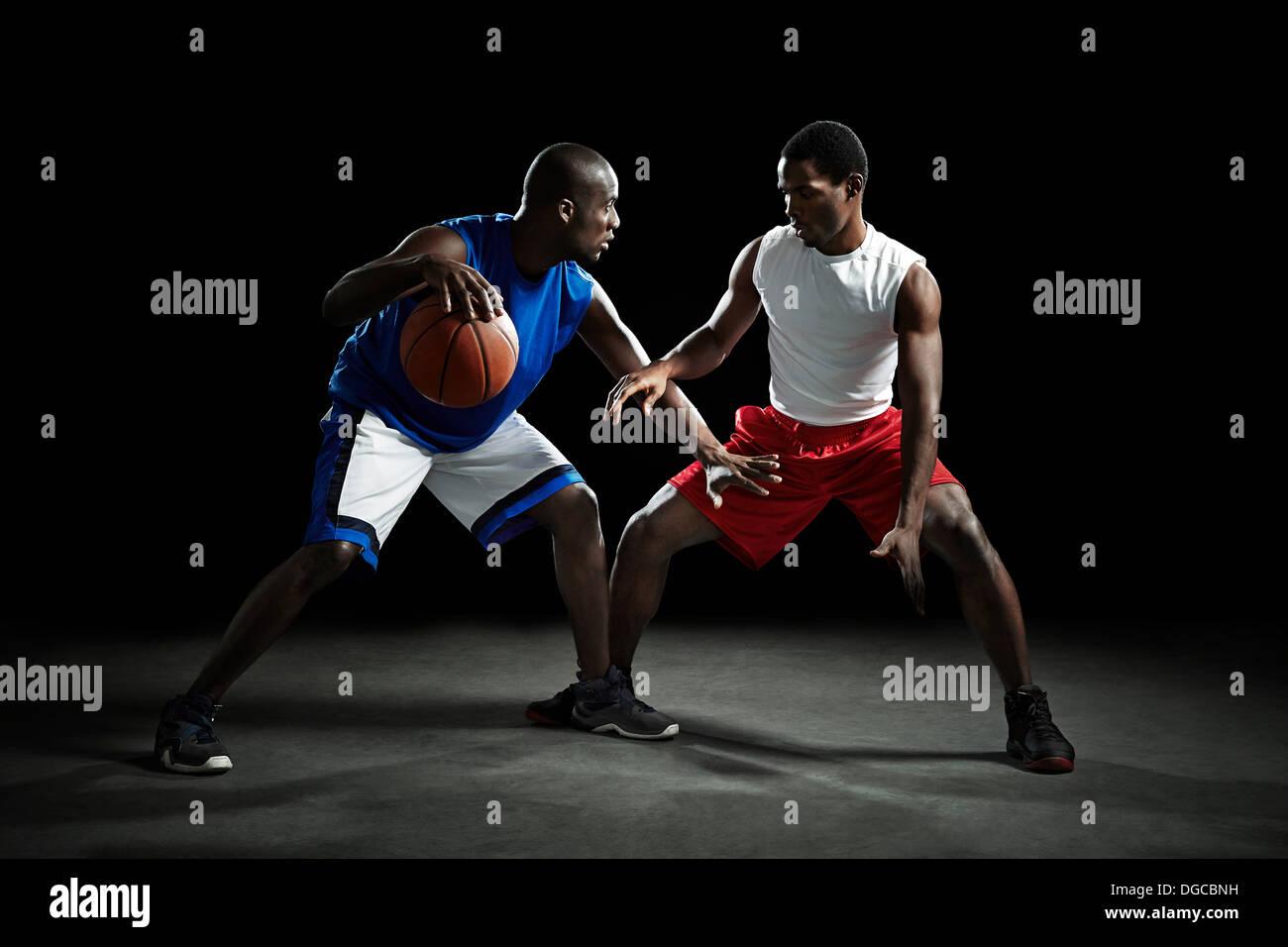 I giocatori di basket in concorrenza per la sfera Immagini Stock